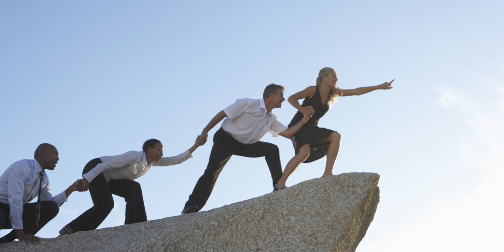 Woman leading three colleagues on rock, pointing