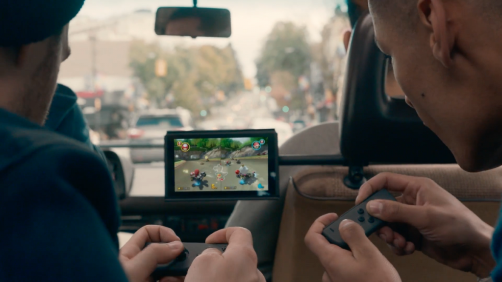 you-can-even-use-the-detachable-controllers-for-local-multiplayer-action-here-two-buddies-race-against-each-other-in-mario-kart-with-each-holding-one-side-of-the-joy-con-controller-jpg